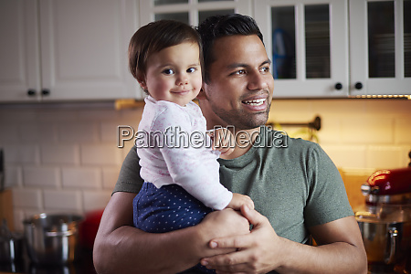 smiling father holding baby girl in