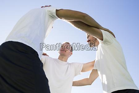 football players huddling on football field