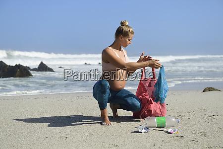schwangere frau reinigung den strand von