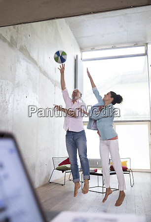 casual businessman and businesswoman playing basketball