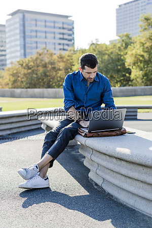 businessman sitting on bench outdoors working