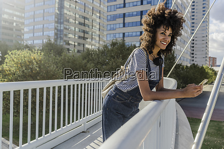 young woman standing on a bridge