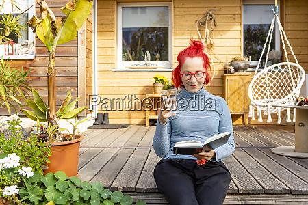 portraet einer laechelnden seniorin mit rot