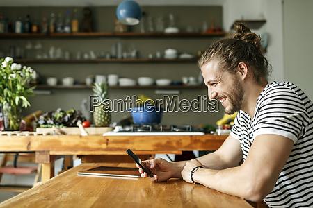 junger mann mit einem broetchen sitzt