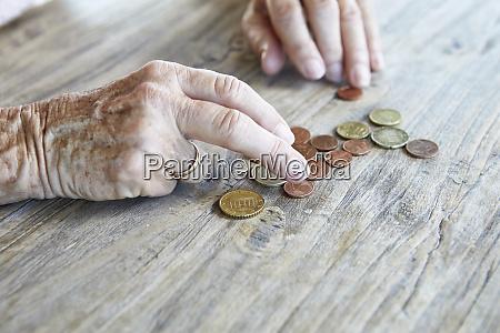 hand von seniorin zaehlen muenzen nahaufnahme