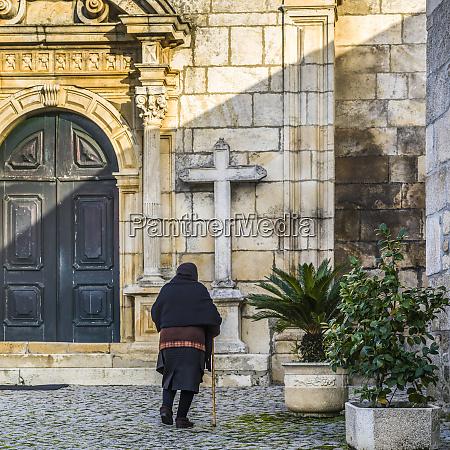 seniorenfrau naehert sich einer kirche gemeinde