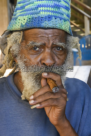 a man smokes a cigar roatan