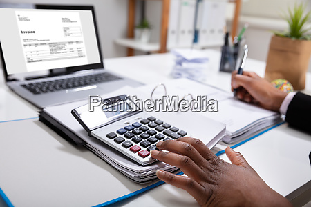 businesspersons calculating invoice using calculator