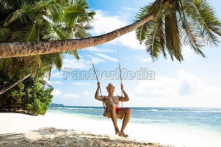 young man enjoying swinging on the