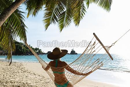 woman in bikini sitting on hammock
