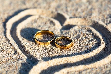 golden wedding rings inside the heart