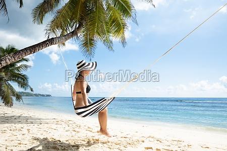 young woman in bikini sitting on