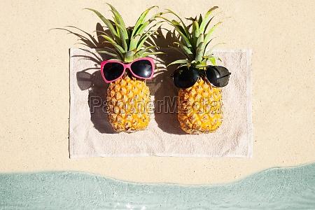 zwei ananas liegen auf handtuch ueber