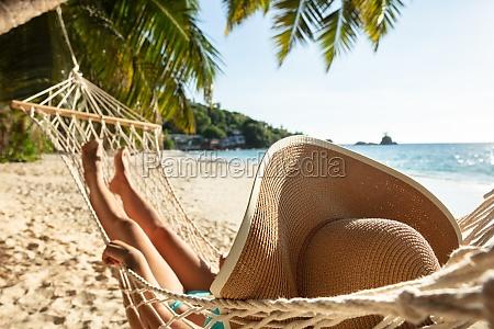 frau im bikini liegend auf haengematte