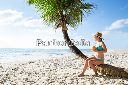 woman in bikini drinking the coconut