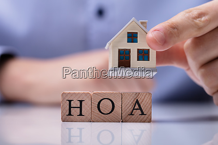businessman placing house models on hoa