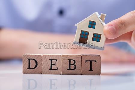businessman placing house models on debt