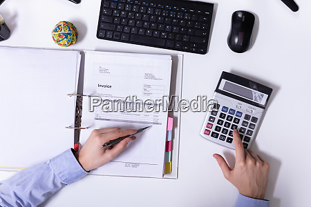 businessman using calculator while calculating invoice
