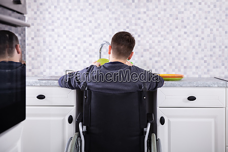 handicapped, man, cleaning, dishes, in, kitchen - 26938923
