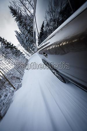 schnelles auto auf winterlich alpiner schneestrasse