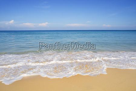 strandsand und blaues meer in blauem