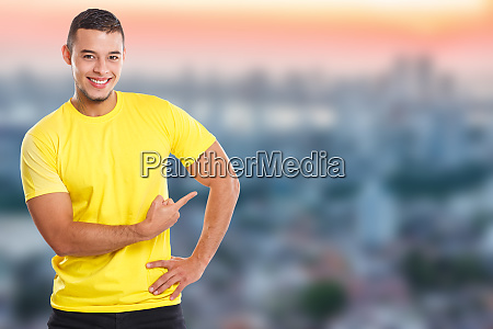 young latin man showing pointing marketing