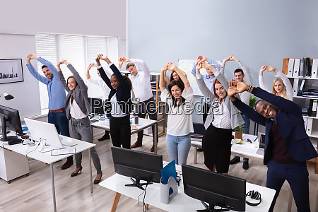 young businesspeople doing stretching exercise at