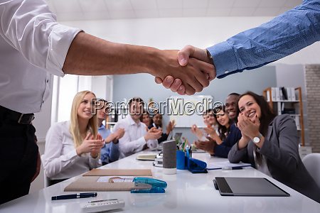 teamleiter haendeschuetteln vor mitarbeiter glueckwunsch