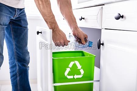 mann wirft plastikflasche in recycling behaelter