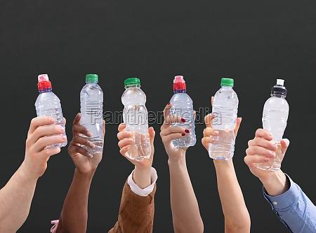 verschiedene menschen die wasserflaschen in einer