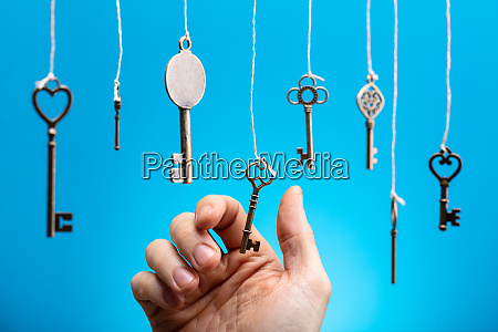 persons hand choosing hanging key