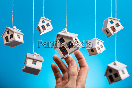 person holding hanging model house