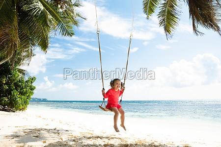 little girl swinging on the beach