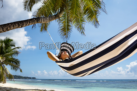 young woman relaxing on hammock over