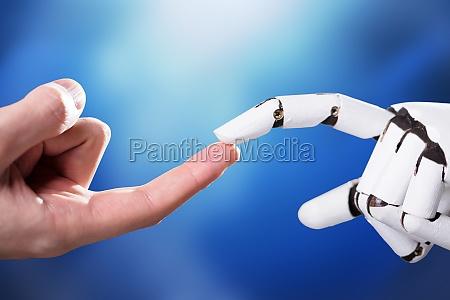 roboter beruehrt den indexfinger des mannes