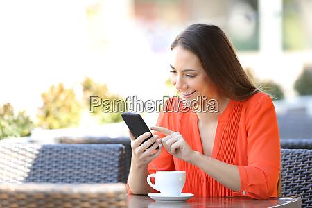 glueckliche frau stoebert ein smartphone in