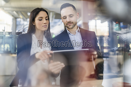 businessman and businesswoman with tablet talking