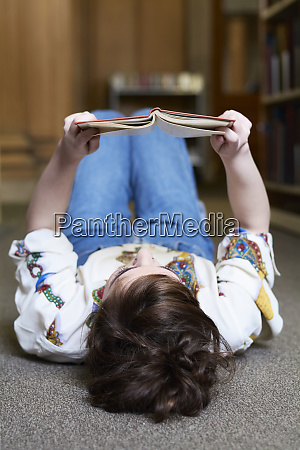 female student reading book in a