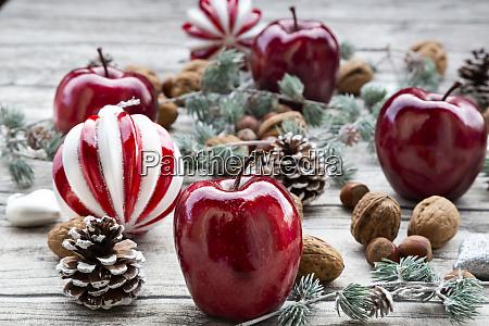 weihnachtsaepfel walnuesse haselnuesse und weihnachtsdekoration auf