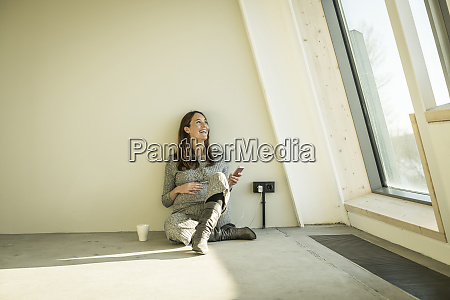 pregnant woman drinking tea sitting on