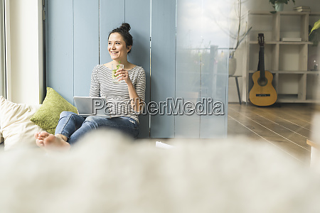 smiling woman sitting at the window