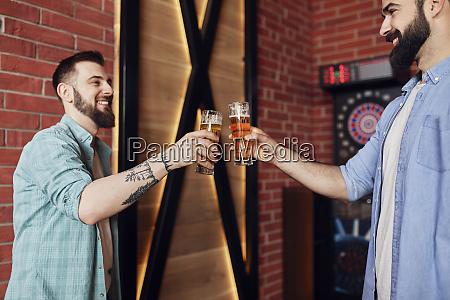 zwei glueckliche freunde klirren bierglaeser an