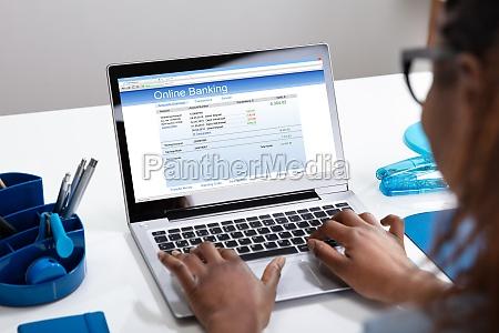geschaeftsfrau die online banking auf laptop