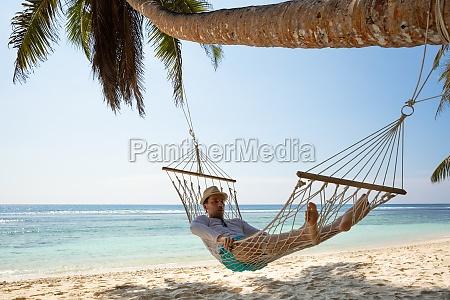 man lying on hammock at beach