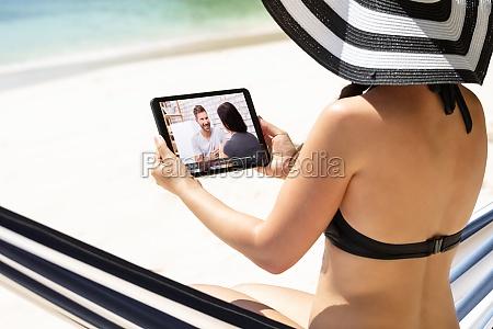 woman in bikini watching video on