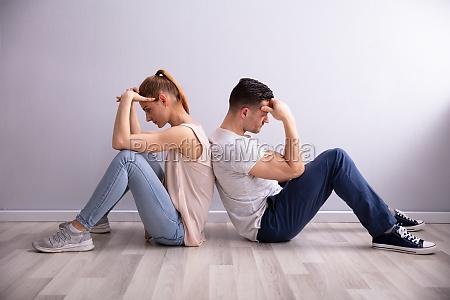 sad couple sitting on floor