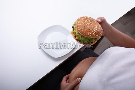 UEbergewichtige frau haelt hamburger in der
