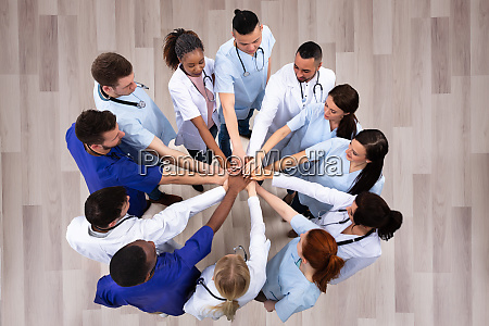 elevated view of doctors stacking hands
