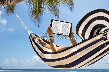 woman in hammock reading the book