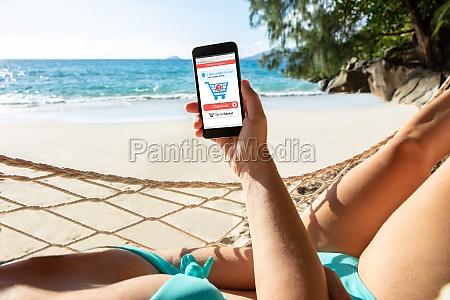 woman in hammock shopping online on